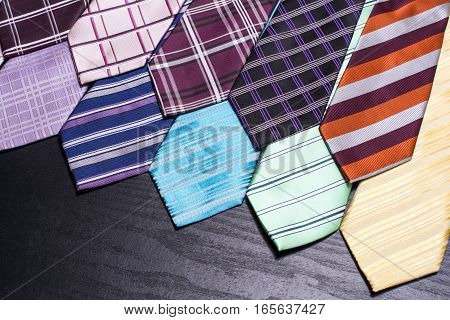 A lot of lined colorful ties facing diagonally on black table