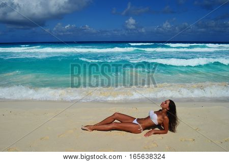 Girl in a white swimsuit is lying on the sea beach
