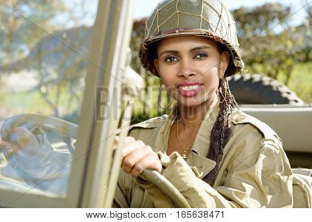 beautiful smiling black young woman with a ww2 military helmet