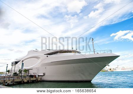 beautiful white yacht luxury modern motor vehicle at moorage in sea port pier shore on summer day on blue cloudy sky
