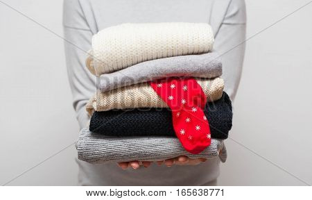 Woman holding stack of sweaters with red sock among them on grey background