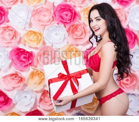 Spring Holidays Concept - Sexy Young Woman In Red Lace Lingerie With Gift Box Over Paper Flowers Bac