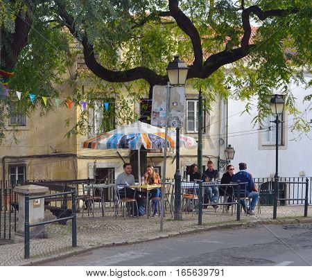 LISBON, PORTUGAL - MARCH 04, 2016: Streets Cafe with people at tables  in the Alfama district  Lisbon Portugal