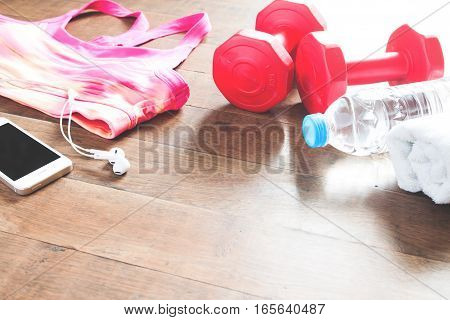 Set of workout equipment and accessories for woman on wood floor. Copy space
