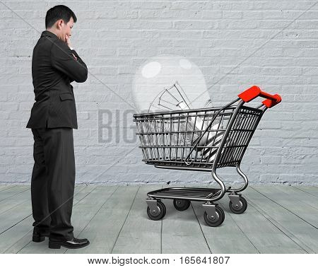Standing Man Looking At Shopping Cart With Large Light Bulb