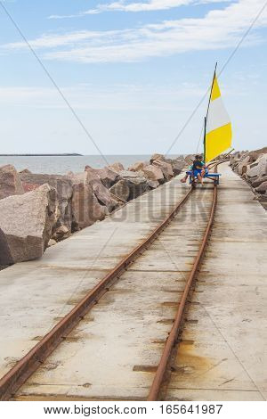 Vagoneta In The Rail Over Breakwater At Cassino Beach