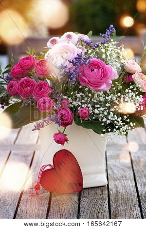 Colorful bouquet with a heart on a wooden table and bokeh for valentines day or mothers day