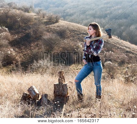 Beautiful sexy smiling woman in jeans and checkered shirt chopping wood with axe. Nature