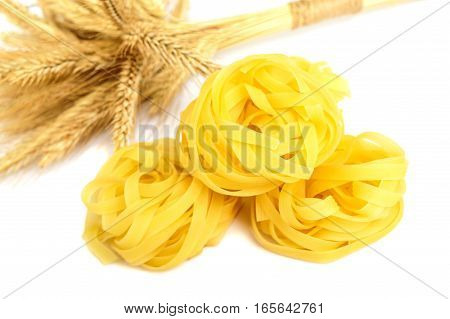 Pasta tagliatelle in a nest and spikelets wheat isolated on white background.