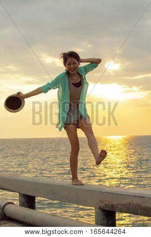 asian woman relaxing summer vacation at sea beach against beautiful sun set sky