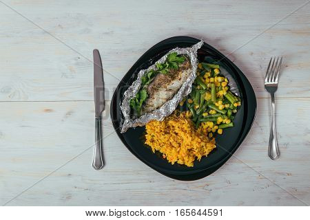 plate with rise fish and vegetables on white wooden background