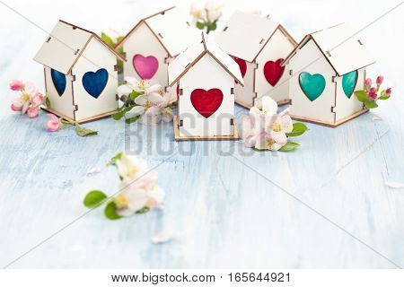 White wooden houses with colorful heart shaped windows.