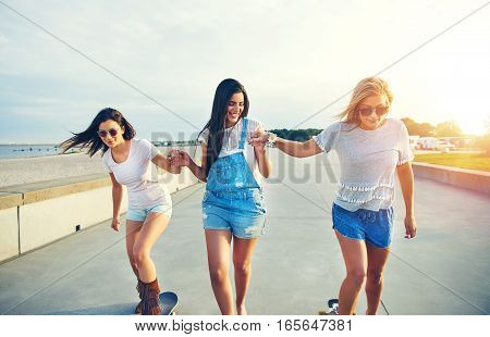 Three Young Cheerful Girls Skateboarding In Sunlight