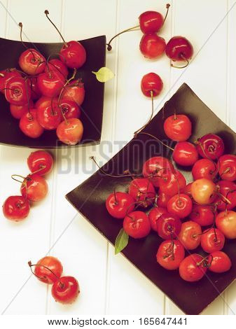 Arrangement of Two Black Plates with Fresh Ripe Sweet Maraschino Cherries closeup on Plank White background. Retro Styled