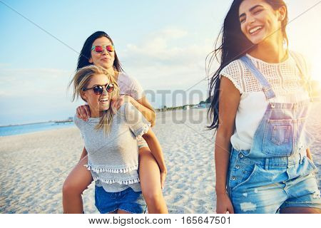 Three Happy Female Friends Walking On Beach