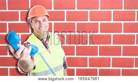 Smiling Young Builder Giving The Telephone