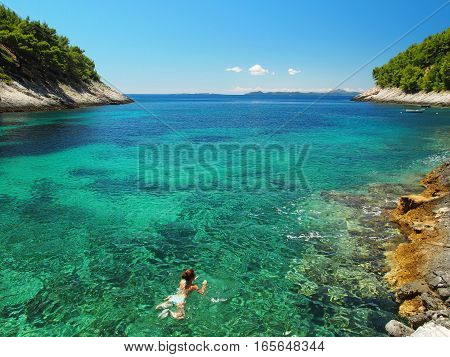 Woman swimming in the bright, clear sea