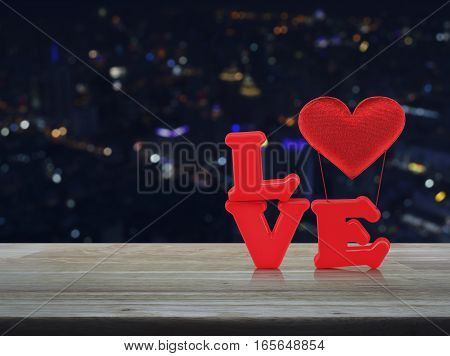 Red love alphabet and fabric heart on wooden table over blur colourful night light city tower Valentines day concept