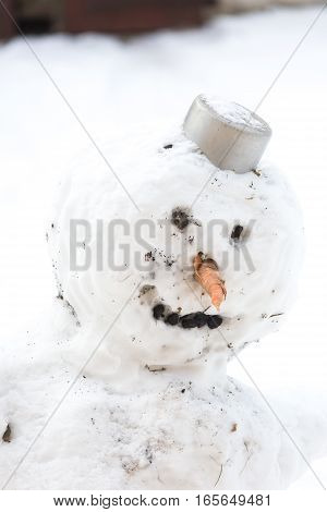 Snowman standing outdoor portrait. Funny traditional snow sculpture. Snowman with carrot nose and pot on his head.