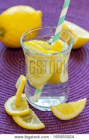 Lemonade with fresh lemon. Lemon water on a purple napkin.