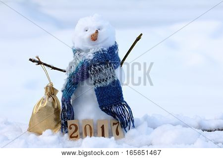 merry snowman in a warm scarf holding bag with gifts on the background of a snowy landscape / winter mood happy 2017