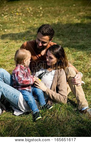Happy Joyful Young Family With Child. Father, Mother And Little Boy Having Fun Outdoors In Orchard G
