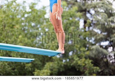 Female diver standing on a springboard preparing to dive in to swimming pool