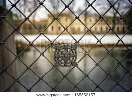Fence Closeup With River And Historic Building