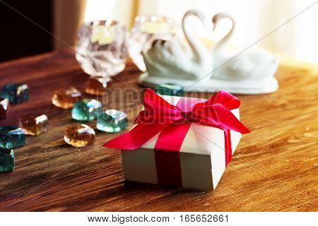 Valentine's Day concept. Gift with red bow on the wooden background Valentines. Valentines gift boxes tied with a red satin ribbon bow on background. gift on wedding day