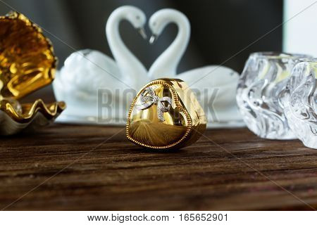 Closeup gold gift box of heart on old wooden table. gold heart-shaped box .Valentine's Day concept.