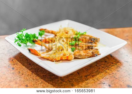 asian seafood fried prawn with garlic in white plate on the orange marble table selected focus