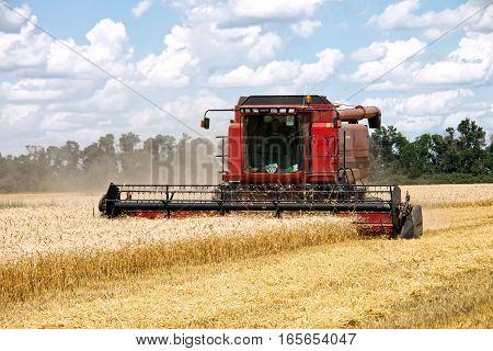 Kharkiv Ukraine - July 12 2011: Combine harvests wheat on a field in sunny summer day in Kharkiv Oblast Ukraine on July 12 2011