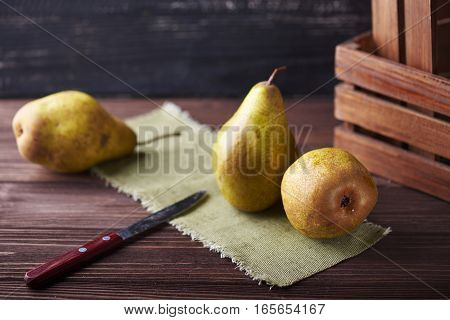 Fresh green pears and knife on a rustic background with napkin and old boxes.