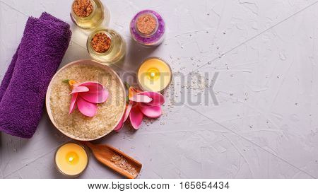 Spa or wellness setting in yellow and violet colors. Bottles with aroma oil sea salt in bowl towel and flowers on grey background. Selective focus. Place for text.