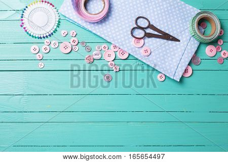 Sewing thread - buttons scissors fabric on turquoise wooden background. Selective focus. Scrapbboking. Flat lay. Place for text.