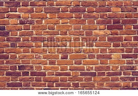 a brickwork texture containing different sized and colored bricks with gray seams in a dark vintage looking color tone. The brick wall with individual structure can be used as background pattern or for titles.