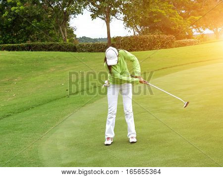 Smiling woman golf player putting successfully ball on green ball dropping into cup