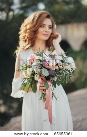 The bride with a bouquet on beautiful large lake background at sunset. Rustic Wedding