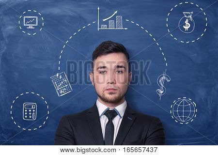 Businessman on blue blackboard background with chalk drawing of small charts, graphs, money sack and calculator around him. Business and money. Statistics and data. Calculating profit.