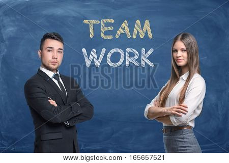 Businessman and businesswoman on blue chalkboard background with words 'Team Work'. Workplace communication. Colleagues and friends. Goals achievement.