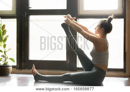 Young attractive woman practicing yoga, sitting in Heron exercise, Krounchasana pose, working out, wearing sportswear, grey pants, bra, indoor full length, home interior background, floor window