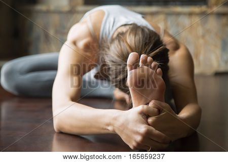 Close up of young woman practicing yoga, sitting in Head to Knee Forward Bend exercise, Janu Sirsasana pose, working out, wearing sportswear, grey pants, bra, indoor, home interior background