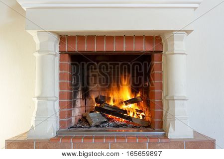 Fireplace burning. Warm cozy burning fire in a brick fireplace close up. Cozy background.
