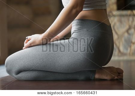 Young woman practicing yoga, sitting in seiza exercise, vajrasana pose, working out, wearing sportswear, grey pants, indoor, home interior background. Midsection close up