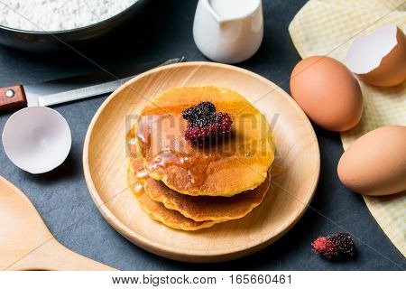 Pancakes with fresh mulberry and honey on black stone background