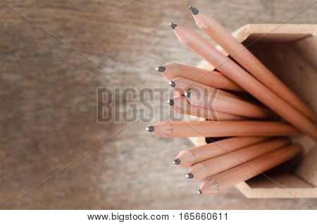 Close up of pencils in holder with wooden background