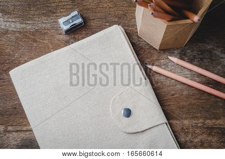 Brown diary cover with pencils and pencil sharpener on wooden background