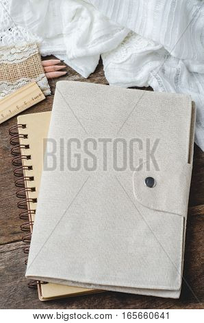 Blank daily notebook with color pencils and ruler on wooden background