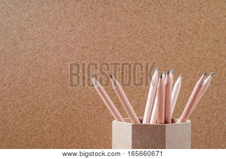 Close up of pencils in wooden holder with brown background