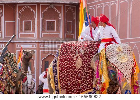 April 15 2016. Indian men part of a royal wedding procession the baraat wait for the bride and groom while dressed in traditional clothes and sitting on a beautifully decorated elephant.